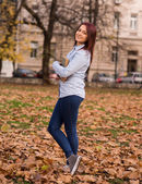 Redhead girl standing and holding a book in park — Stock Photo