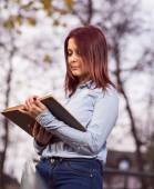 Redhead student girl reading a book in park — Stock Photo