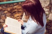 Redhead girl sitting on stairs and reading a book — Stock Photo