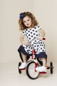 Girl in spotty dress on tricycle — Stock Photo