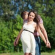 Happy and young pregnant couple hugging in nature — Stock Photo #58614819
