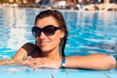 Beautiful long hair young woman in blue water in sunglasses, close up outdoor portrait — Stok fotoğraf