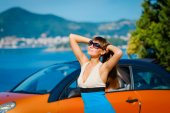 Beautiful young woman with long hair standing near orange cabriolet at the Mediterranean sea coast  — Stock Photo