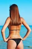 Sexy back of a beautiful woman in bikini on sea background. Sexy buttocks — Stock Photo