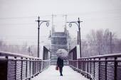 Young woman is going across the bridge in snowfall toned image — Stock Photo