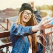 Young sexy blonde hipster woman posing for selfie and laughing. Wearing jeans jacket, hipster black hat and glasses. Lifestyle portrait bright with sun shine. — ストック写真 #75346333