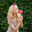 Fashion outdoor portrait of beautiful elegant blonde woman wearing pin up style, posing with rose lollipop. Green nature background. Retro vintage toned image, film simulation. — Stock Photo #75347265