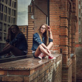 Outdoor lifestyle portrait of pretty young sitting girl, wearing in hipster swag grunge style urban background. Retro vintage toned image, film simulation. — Stock Photo