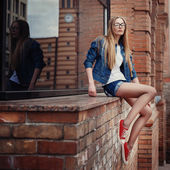 Outdoor fashion lifestyle portrait of pretty young sitting girl, wearing in hipster swag grunge style urban background. — Stock Photo