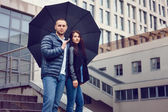 Beautiful young couple in love on a date outdoors on modern urban background. Bearded handsome man and brunette pretty woman in casual dress with umbrella. Rainy weather. — Stock Photo