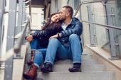 Beautiful young couple in love on a date outdoors on modern urban background. Smiling and hugging. Bearded handsome man and brunette pretty woman in casual dress. — Stock Photo