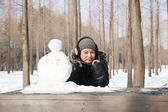 Asian beautiful woman building snowman in garden — Stock Photo