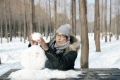 Asian handsome guy building snowman in garden — Stock Photo