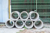 Concrete drainage pipes stacked for construction, irrigation, in — Stock Photo