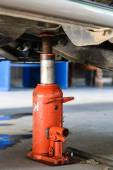 Car with a jack to lift the wheel for repair. In the garage — Stock Photo