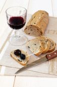French bread with olives, Provencal olives and a glass of red wi — Stock Photo