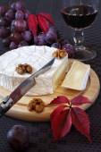 French cheese Coulommiers, grapes, autumn leaves and glass of re — Stock fotografie