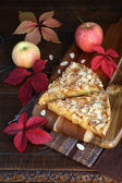 Apple pie, colorful leaves on an old wooden surface — Stock Photo