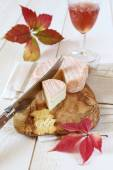 Autumn composition: red leaves, French cheese and wineglass — Stock Photo