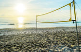 Sunrise on the beach and volleyball net — Stockfoto