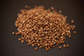 Buckwheat pile on a black stone background — Stock Photo