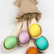Colorful Easter eggs in wooden spoons on white background — Stock Photo #68103667
