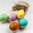 Colorful Easter eggs in wooden spoons on white background — Stock Photo #68103673