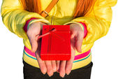 Giving gift with hands holding a red gift. — Stock Photo