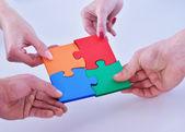 Business people assembling jigsaw — Stock Photo