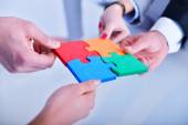 Business people assembling jigsaw — Stock Photo