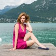 Beautiful woman in a pink dress sitting at the pier. — Stock Photo #78124816