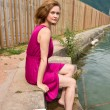 Pretty woman in pink dress sitting near the pier. — Stock Photo #78124526