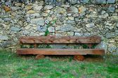 Wooden Bench in Front of a Rock Wall — Stock Photo