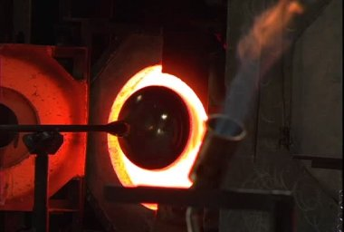 A glassblowing artist pushes a hot glass jar into an oven — Stock Video