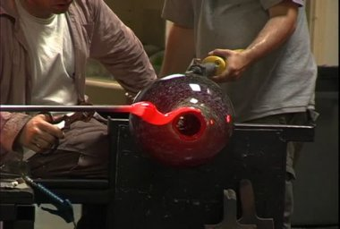A team of glassblowers mold and shape a hot glass jar. — Stock Video