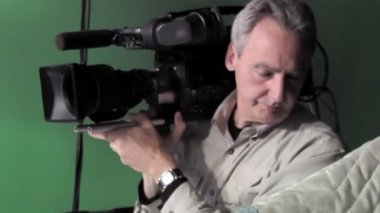 Cinematographer records hand-held in a studio. — Vídeo de stock
