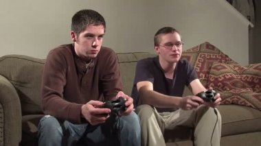 Two guys playing video games on a couch. — Vídeo Stock