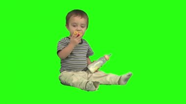 Small boy sitting and holding a bottle with a milk and pacifier in the mouth — Stock Video