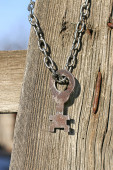Rusty key hanging on a wooden fence — Stock Photo