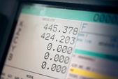 CNC machine monitor display with program code running and numbers with parameters changing — Stock Photo