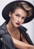 Portrait of sensual woman in hat leather jacket  in studio — Stock Photo