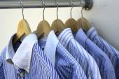 Shirts on wooden hangers — Stock Photo