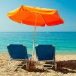Blue sunbeds and orange umbrella (parasol) on Paradise Beach in — Stock Photo #61642903