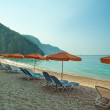 Blue sunbeds and orange umbrella (parasol) on Paradise Beach in  — Stock Photo #61642943