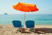 Blue sunbeds and orange umbrella (parasol) on Paradise Beach in  — Foto de Stock