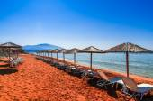 Straw umbrellas and sunbeds on a red sand beach and turquoise wa — Stock Photo