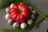 Tomato with avocado and garlic with dill. on wood background — Stock Photo