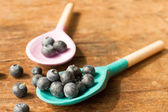 Blueberries and wooden spoon on a wooden tray — Stock Photo