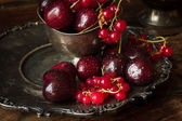 Cherry with red currants in a bowl and a metal plate in oriental — Stock fotografie