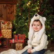 Little boy sitting near a Christmas tree — Stock Photo #65465927